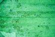 Leinwanddruck Bild - Fragment of old house wall close-up. Green background. Peeling plaster on concrete surface. tinted green. Cracks in paint. Copy space. Place for text. Selective focus image.