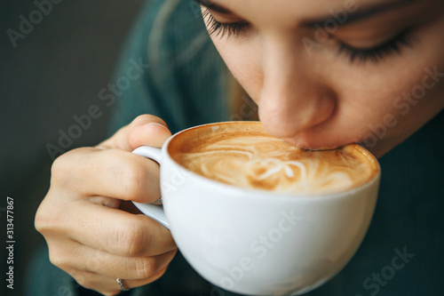 Slika na platnu Close up girl is drinking coffee