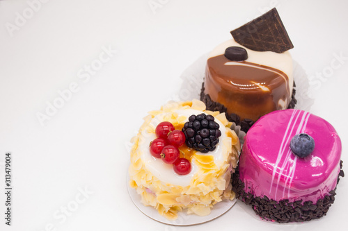 Fotografía  Three cakes on a white background:coffee cake with a grain of coffee, chocolate,