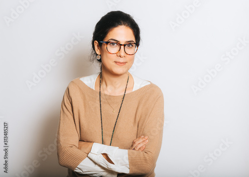 Obraz Studio portrait of beautiful brunette woman, wearing glasses, arms crossed, posing on white background - fototapety do salonu