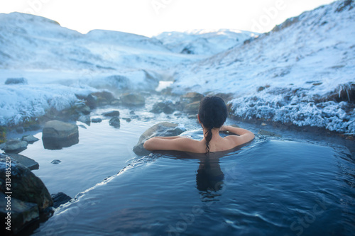 The girl bathes in a hot spring in the open air with a gorgeous view of the snowy mountains Fototapete