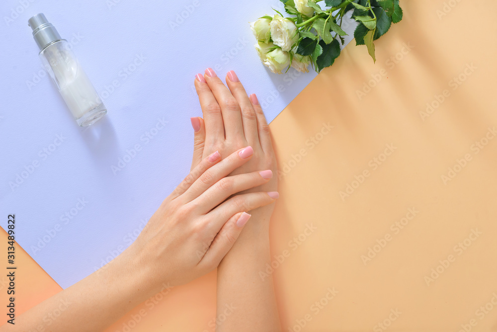 Fototapeta Hands of young woman and bottle of cream with flowers on color background