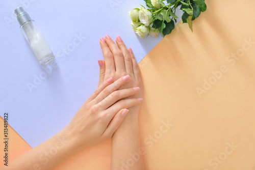 Obraz Hands of young woman and bottle of cream with flowers on color background - fototapety do salonu