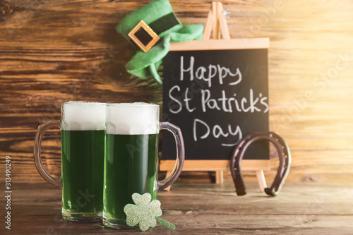 Obraz Mugs of green beer for St. Patrick's Day on wooden table - fototapety do salonu