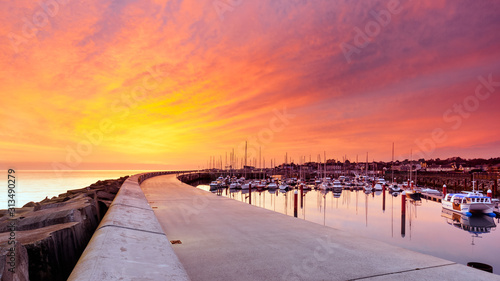 Fotografia, Obraz Amazing sky on sunrise at Greystones yacht marina or harbour with anchored boats and long illuminated pier