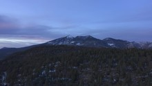 Short Aerial Clip, Approaching Mountain Top With Pine Trees Viewing A Snow Capped Mountain In The Distance On A Cloudy Day While Slightly Panning Up In Flagstaff Arizona