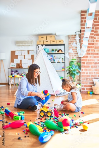 Fototapeta Caucasian girl kid playing and learning at playschool with female teacher. Mother and daughter at playroom around toys playing with bulding blocks obraz na płótnie