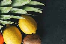 Tropical Fruits Lemon, Kiwi, Pineapple Leaves On Dark Background, Top View, Copy-space