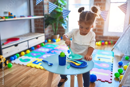 Obraz Young beautiful toddler playing with cutlery and food toys on the table at kindergaten - fototapety do salonu