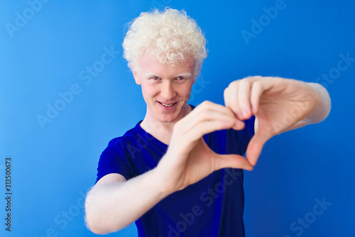 Young albino blond man wearing casual t-shirt standing over isolated blue background smiling in love showing heart symbol and shape with hands Wallpaper Mural