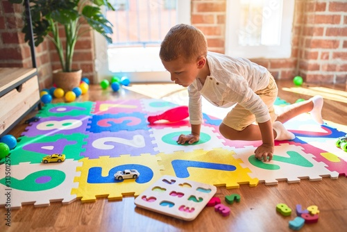 Obraz Beautiful blonde toddler playing with small cars around lots of toys at kindergarte - fototapety do salonu