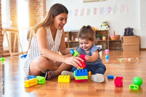 Photo Young beautiful teacher and toddler playing with building blocks toy at kinderga
