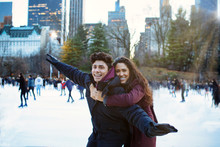 Portrait Of A Happy Young Couple Smiling, Hugging And Having Fun While Ice Skating Outside In Central Park, NYC