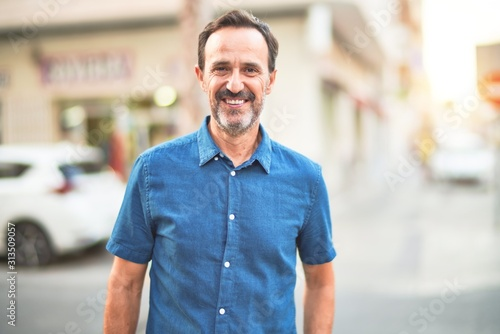 Obraz Middle age handsome man standing on the street smiling - fototapety do salonu