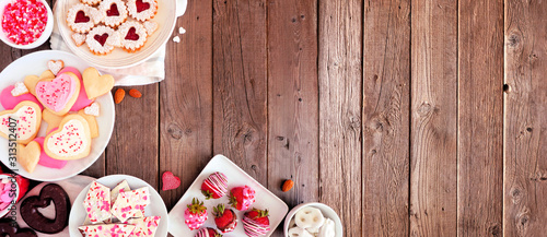 Valentines Day corner border banner of various sweets and cookies. Top view over a wooden background. Love and hearts theme. Copy space. - 313512407