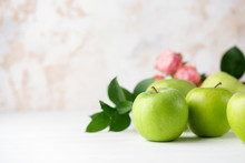 Green Apples With Green Leaf And Flowers On White Table. Copy Space For Text. Healthy Green Food
