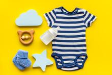 Blue Bodysuit For Baby Boy Near Children's Accessories On Yellow Background Top-down