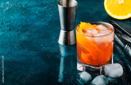 Obraz Orange Alcohol cocktail with red vermouth, bitter, soda, orange zest and ice, dark wooden bar counter background, bar tools, selective focus - fototapety do salonu