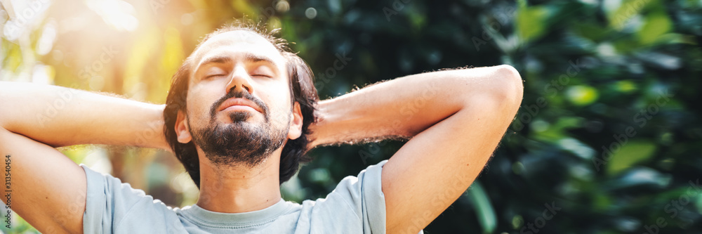 Fototapeta A bearded man is meditating outdoor in the park with face raised up to sky and eyes closed on sunny summer day. Concept of meditation, dreaming, wellbeing healthy lifestyle