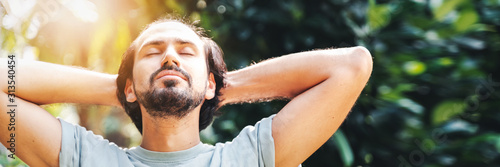 Cuadros en Lienzo A bearded man is meditating outdoor in the park with face raised up to sky and eyes closed on sunny summer day