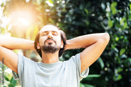 Fotomural A bearded man is meditating outdoor in the park with face raised up to sky and eyes closed on sunny summer day