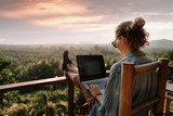 Fototapeta Fototapety z naturą - Young business woman working at the computer in cafe on the rock. Young girl downshifter working at a laptop at sunset or sunrise on the top of the mountain to the sea, working day.