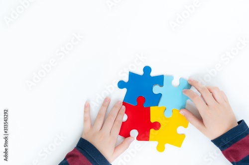 Photo Top view, hands of an autistic child play colorful puzzle which is a symbol of public awareness for autism spectrum disorder - World Autism Awareness day on April 2, Understanding and Acceptance