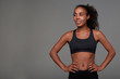 Positive young pretty sporty dark skinned woman with long brown curly hair looking cheerfully aside and keeping hands on her waist, isolated over grey background in athletic wear