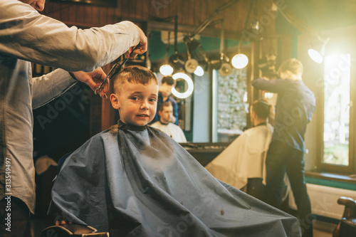 Obraz The child is being cut hairstyles - fototapety do salonu