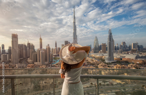 Canvas Print Woman with a white hat is standing on a balcony in front of the skyline from Dub