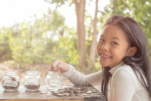 Asian Kid Saving Money Putting Coins Into Glass Bank, Hand Of Little Girl Putting Coins In Jar With Money Stack Step Growing Growth Saving Money, Concept Finance Business Investment, Money Saving