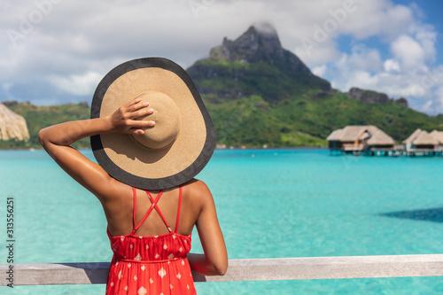 Obraz Beach vacation tourist woman looking at view of Mt Otemanu on Bora Bora luxury resort island on romantic getaway travel vacation. Tourist holding hat from behind enjoying summer holidays. - fototapety do salonu