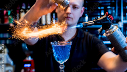 The bartender makes a cocktail with a fire show at the bar Canvas Print