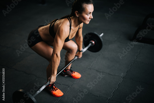 Strong woman bodybuilder with perfect fitness body preparing to lift the heavy barbell from the floor Wallpaper Mural