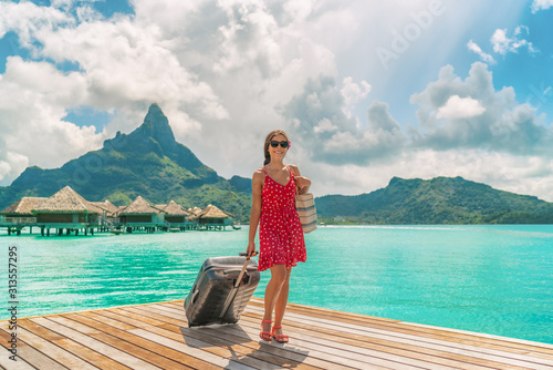 Obraz Hotel luxury resort tourist woman arriving with luggage suitcase in Tahiti Bora Bora honeymoon vacation travel on arrival deck at overwater bungalows. - fototapety do salonu