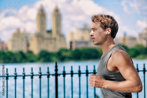 Wireless earbuds man running in Central Park New York city listening to music with wearable technology bluetooth earphone device Wallpaper Mural