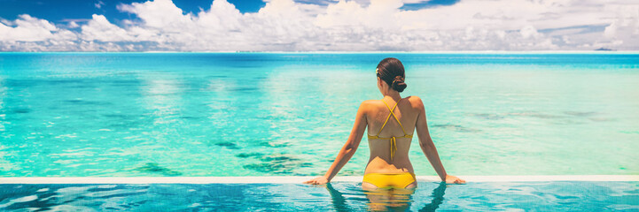 Hotel swimming pool luxury travel vacation summer holiday panoramic banner background with woman in bikini enjoyin sun tan swim lifestyle.