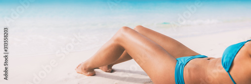 Summer beach bikini body woman lying on white sand sun tanning smooth legs sun tan for laser hair removal concept banner panoramic background Poster Mural XXL