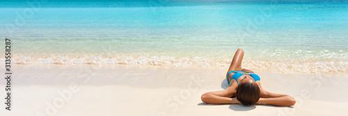 Caribbean suntan woman lying on white sand beach tanning relaxing under the sun in blue bikini Fototapete