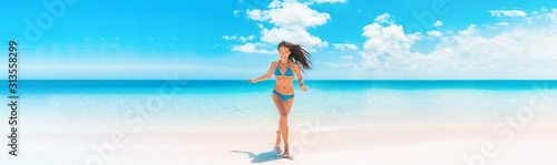 Obraz Beach Asian woman with fit summer bikini body happy running enjoying Caribbean vacation laughing of joy in tropical destination banner panorama. Blue swimwear model enjoying summer holidays. - fototapety do salonu