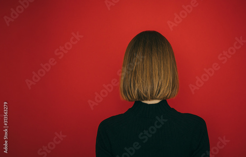 Fotografía Girl with bob hairstyle stands with her back against a red background