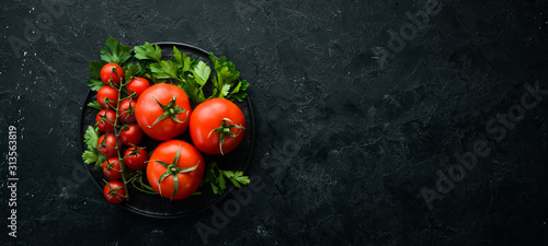 Obraz Fresh red tomatoes on a dark background. Vegetables. Top view. Free space for your text. - fototapety do salonu