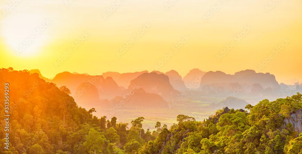 Fototapeta Beautiful panorama landscape with dramatic sunset, tropical rainforest and steep mountain ridge on horizon. Krabi, Thailand