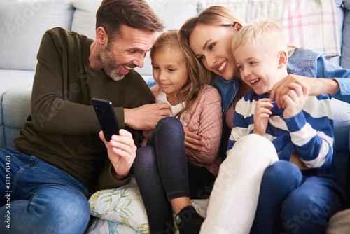 Fototapeta Family using mobile phone in living room obraz