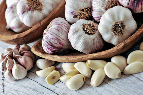 Garlic Cloves and Bulb in wooden bowl on white table. Canvas Print