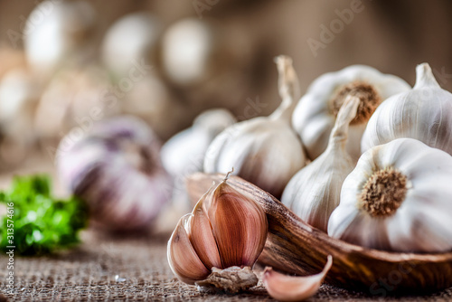 Leinwand Poster Garlic clove and bulbs in wooden bowl