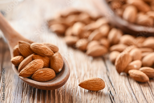 Photo Almond nuts on wooden table top view. Fresh almonds copy space.