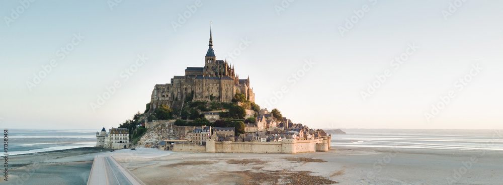 Fototapeta Le Mont Saint Michel tidal island in beautiful twilight at dusk, Normandy, France shot from aerial perspective