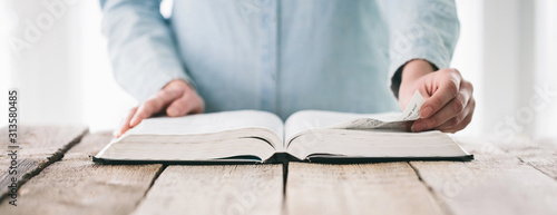Obraz Hands turning the page of a bible. Woman reading a big book or a Bible - fototapety do salonu