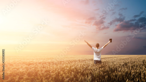 Man holding up Bible in a wheat field during sunrise. panoramic shot
